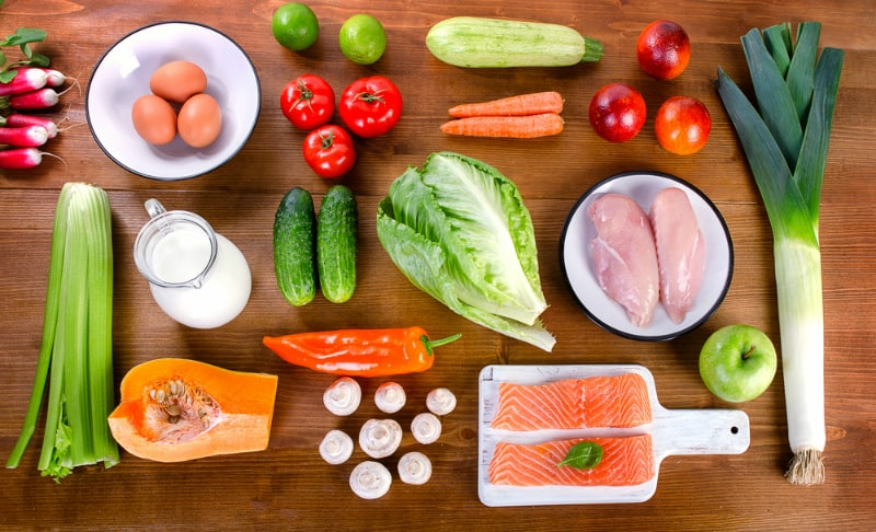 Vegetables, fruit, fish, milk and meat on wooden background. Balanced diet. Healthy eating concept. View from above