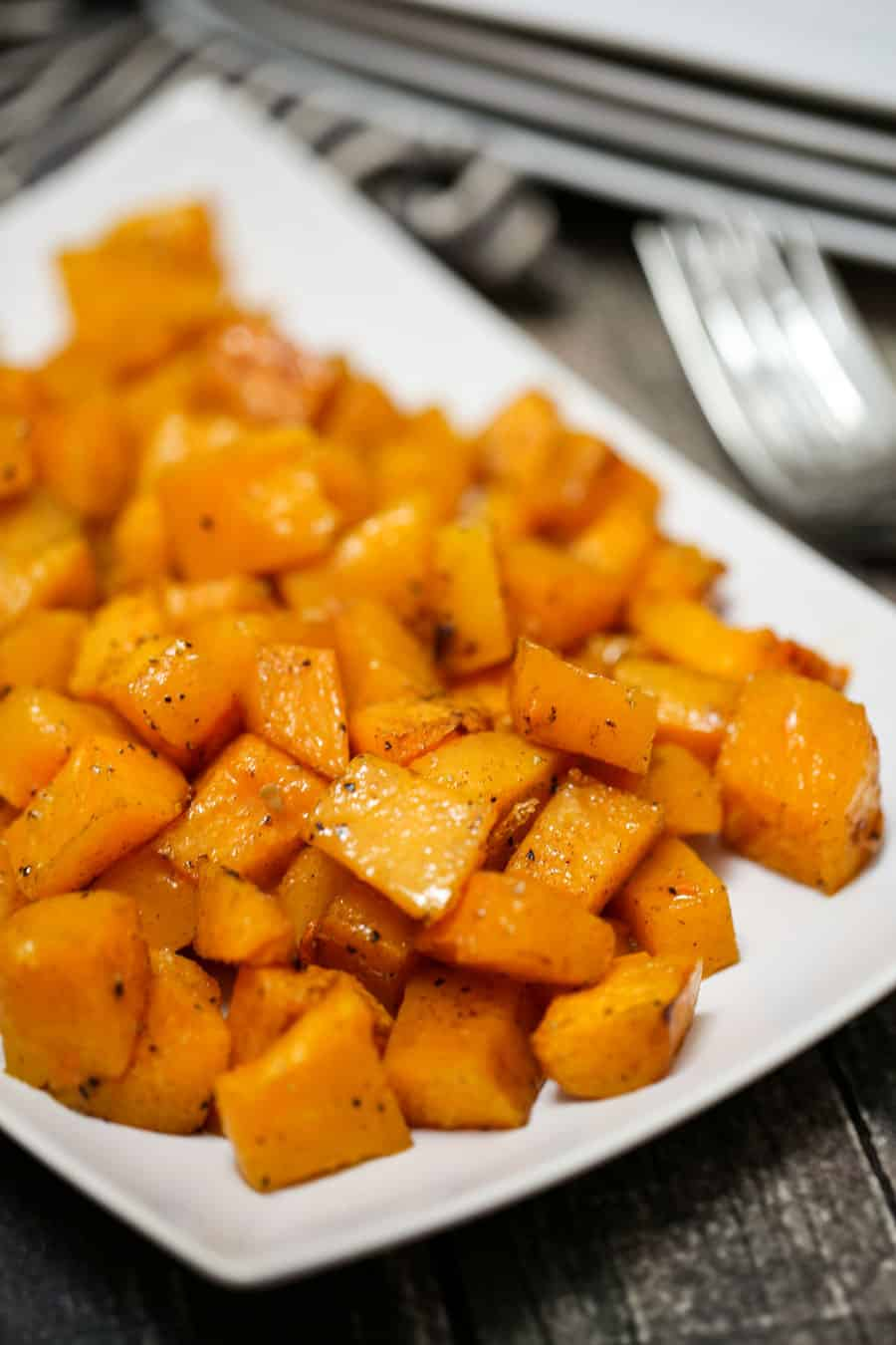 Vitamin packed Roasted Maple Cinnamon Butternut Squash is simple to bake - simply spread butternut squash chunk cubes on a baking sheet which were tossed in olive oil, maple syrup, cinnamon, salt and pepper. The result is a sweet caramelized roasted root vegetable that is a delicious side dish.