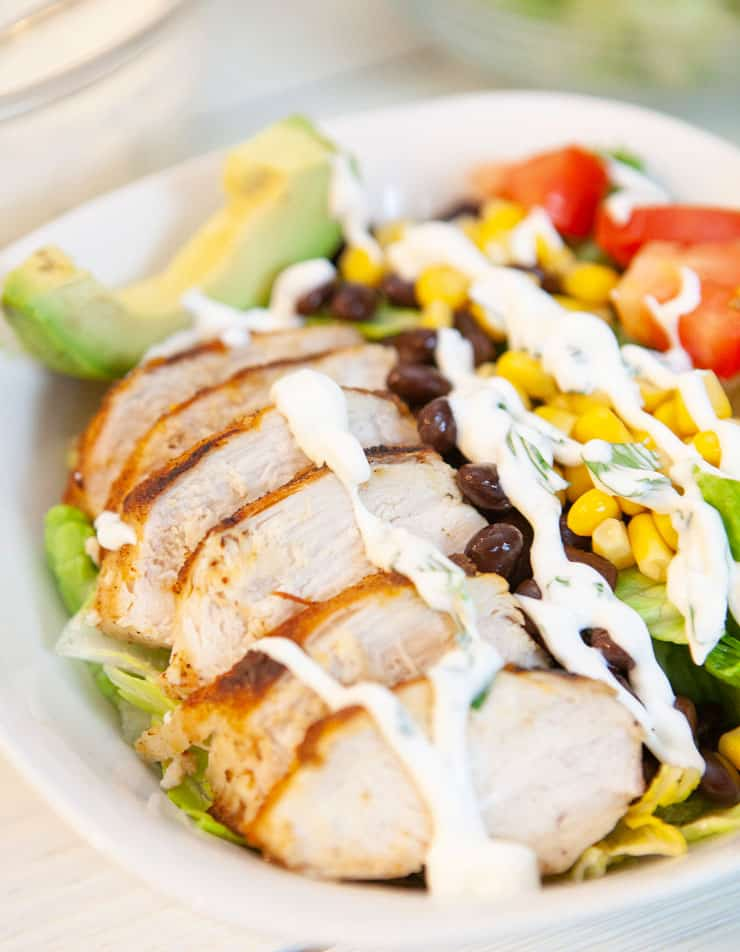 Southwest Grilled Chicken Salad is light, healthy and fresh - full of vegetables and topped with warm spicy chicken, avocado and a creamy cilantro dressing.