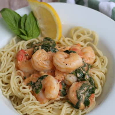 shrimp and pasta in a white bowl on a table