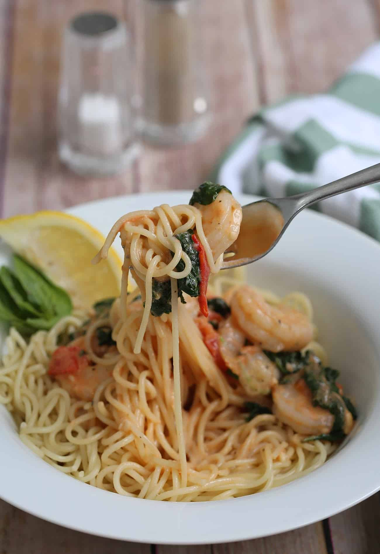 tuscan shrimp and pasta on a fork being lifted from a white bowl