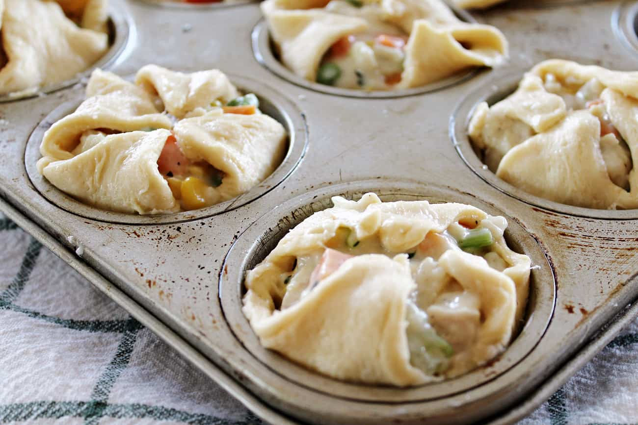 uncooked mini chicken pot pies in a muffin tin with crescent rolls