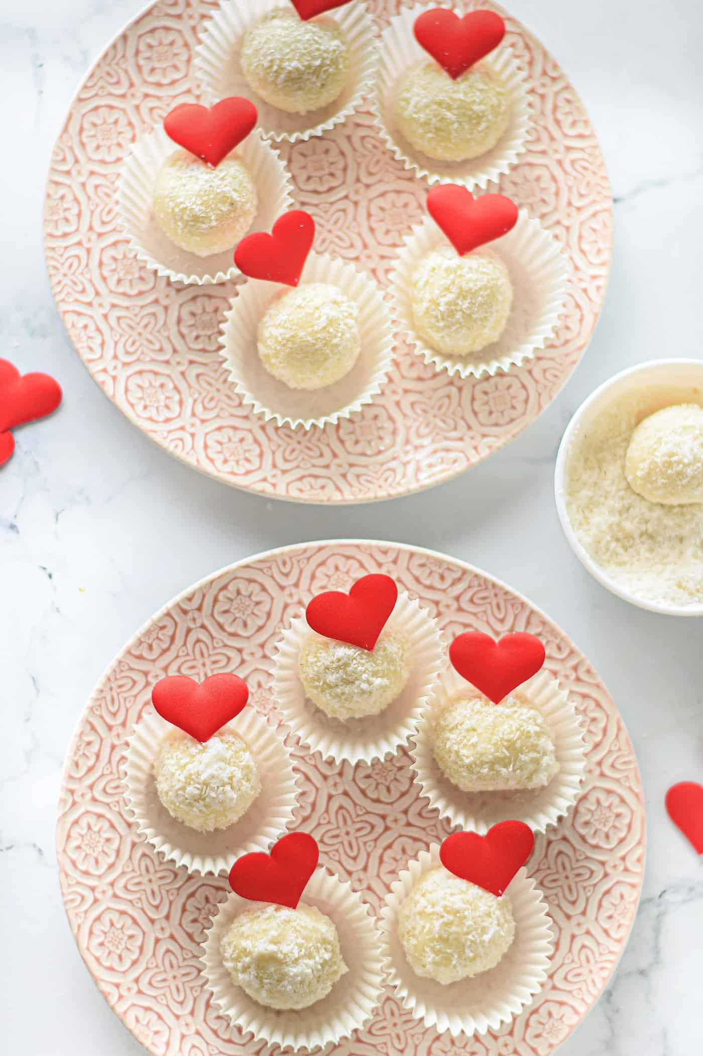 white chocolate coconut truffles in cupcake liners on a plate for valentine's day