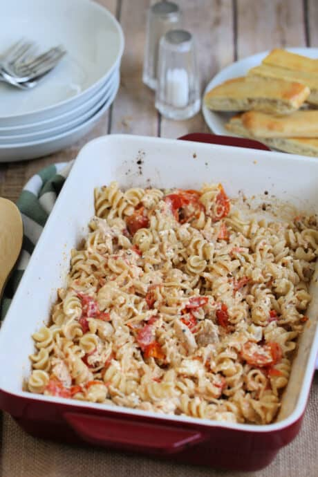 baked feta pasta with chicken in a dish on the table with plates