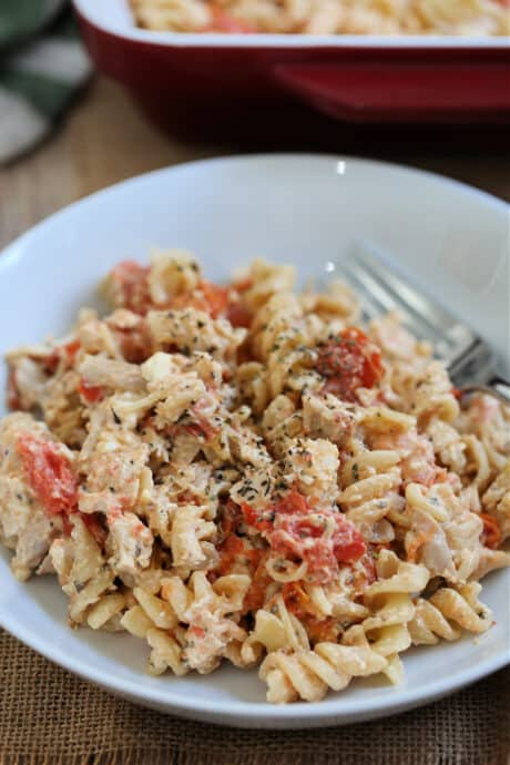 baked feta pasta with chicken in a bowl with a fork