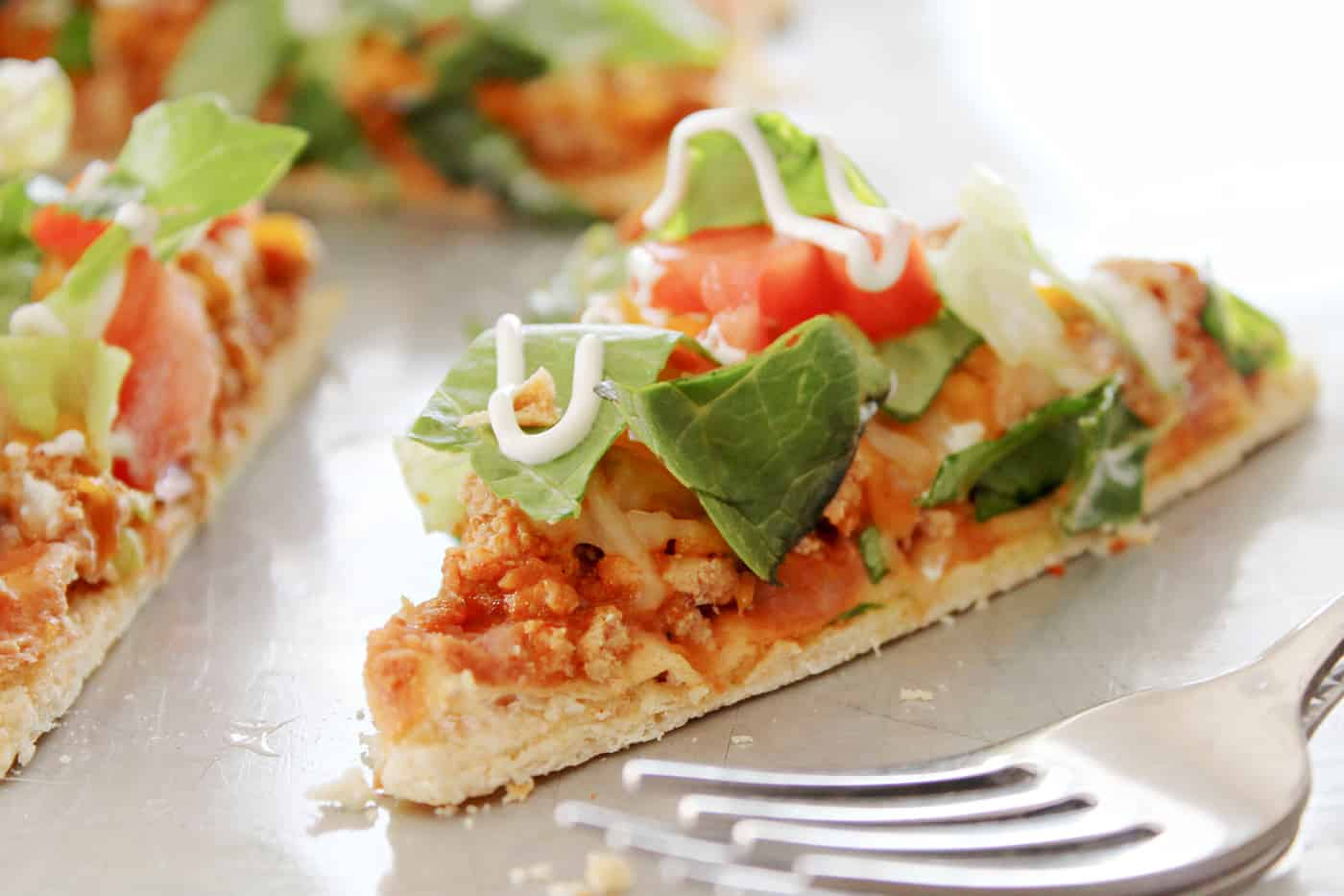 flatbread pizza slice on a plate with a fork