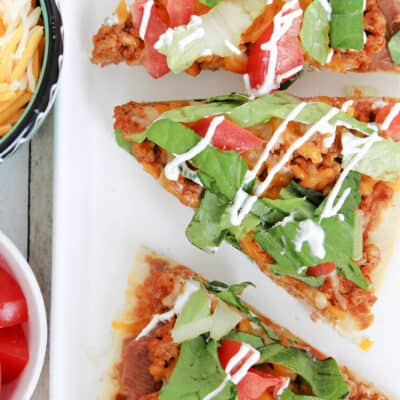 flatbread pizza slices on a plate with a bowl of cheese and tomatoes