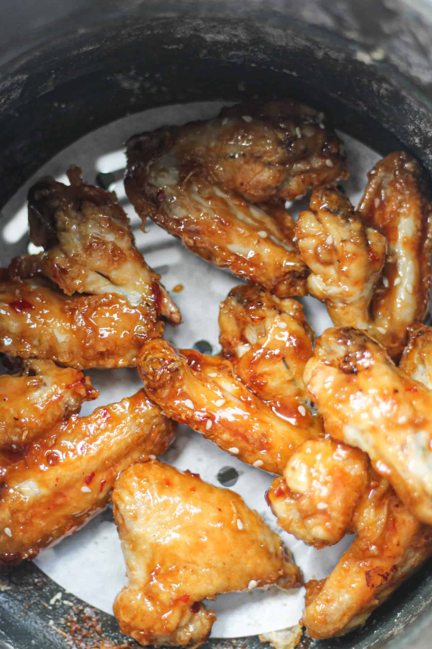sweet chili chicken wings in an air fryer basket