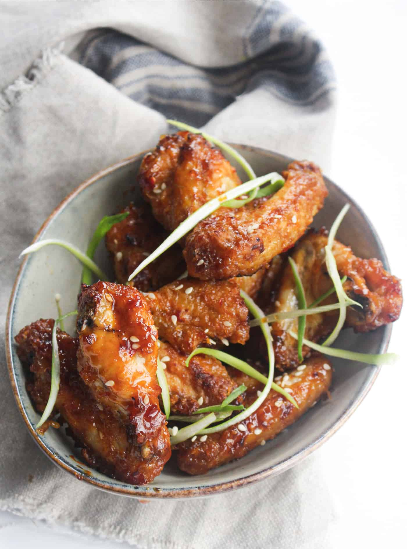 cooked crispy air fryer chicken wings in a bowl with green onion topping