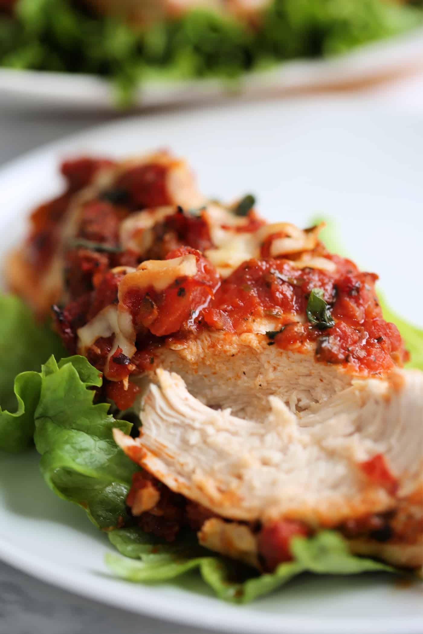 a piece of bruschetta chicken cut open on a plate