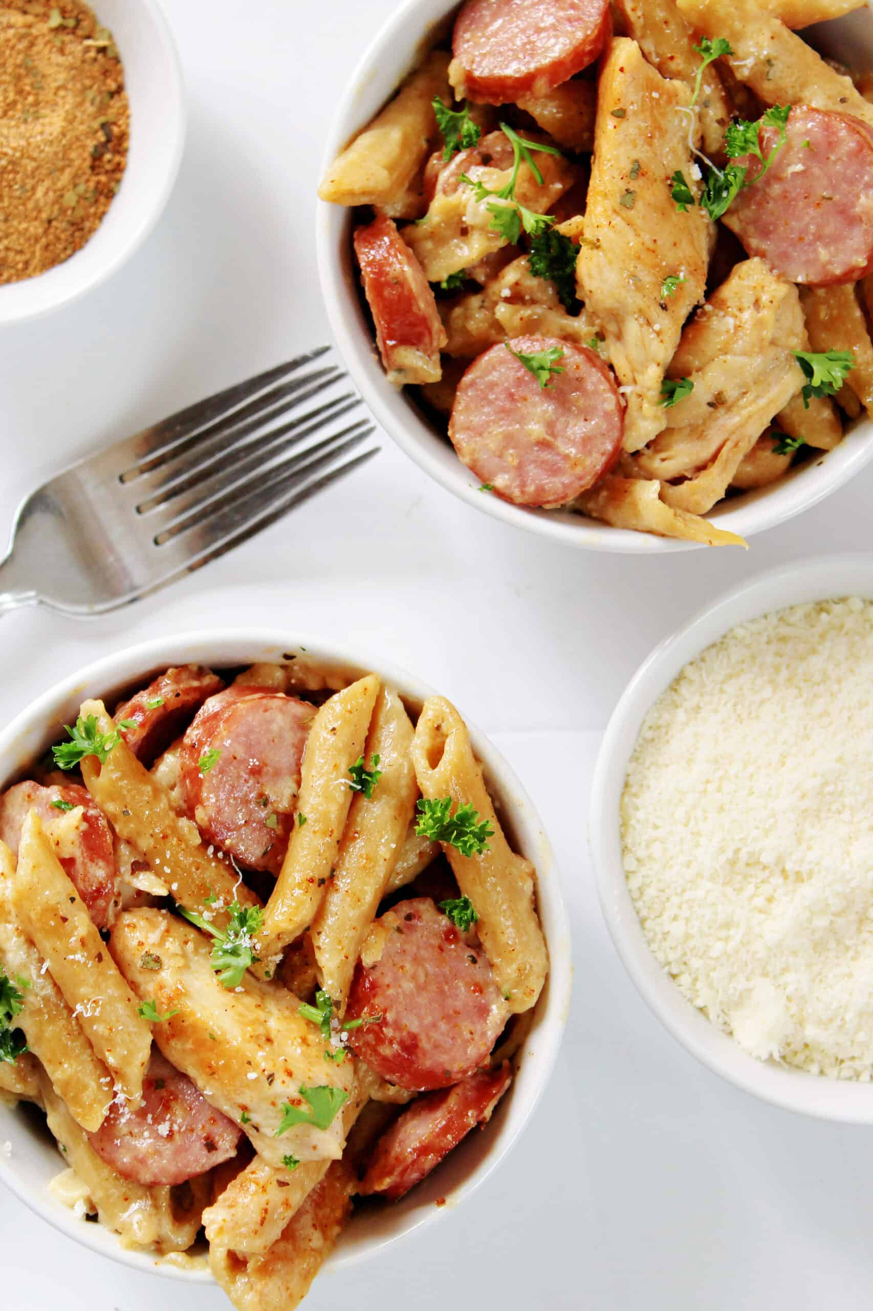 cajun chicken alfredo pasta with sausage in two white bowls with forks