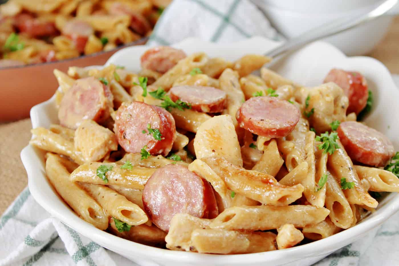 sausage chicken and pasta in a white bowl
