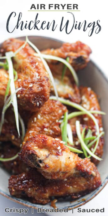 cooked chicken wings in a bowl with green onions and text