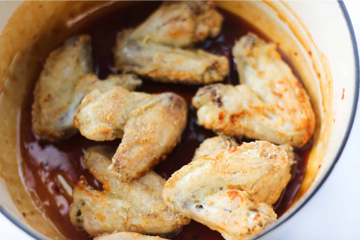 cooked breaded chicken wings in a bowl of sauce