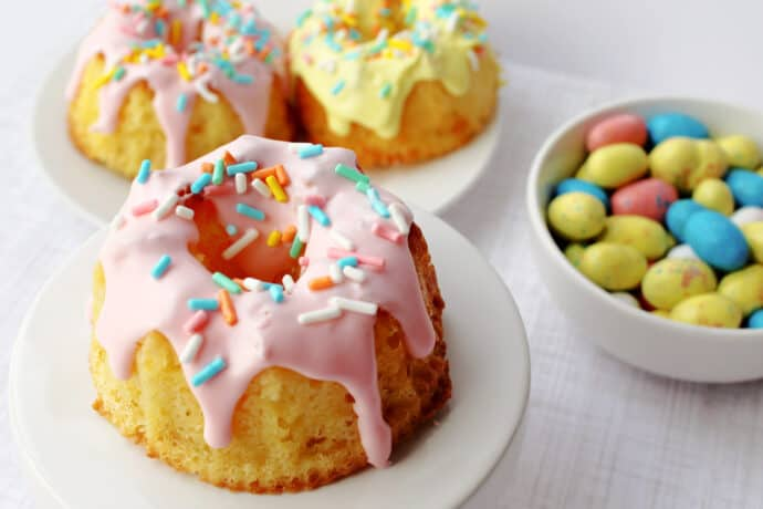 mini bundt cake decorated for spring on a cake stand with a bowl of mini easter chocolate eggs