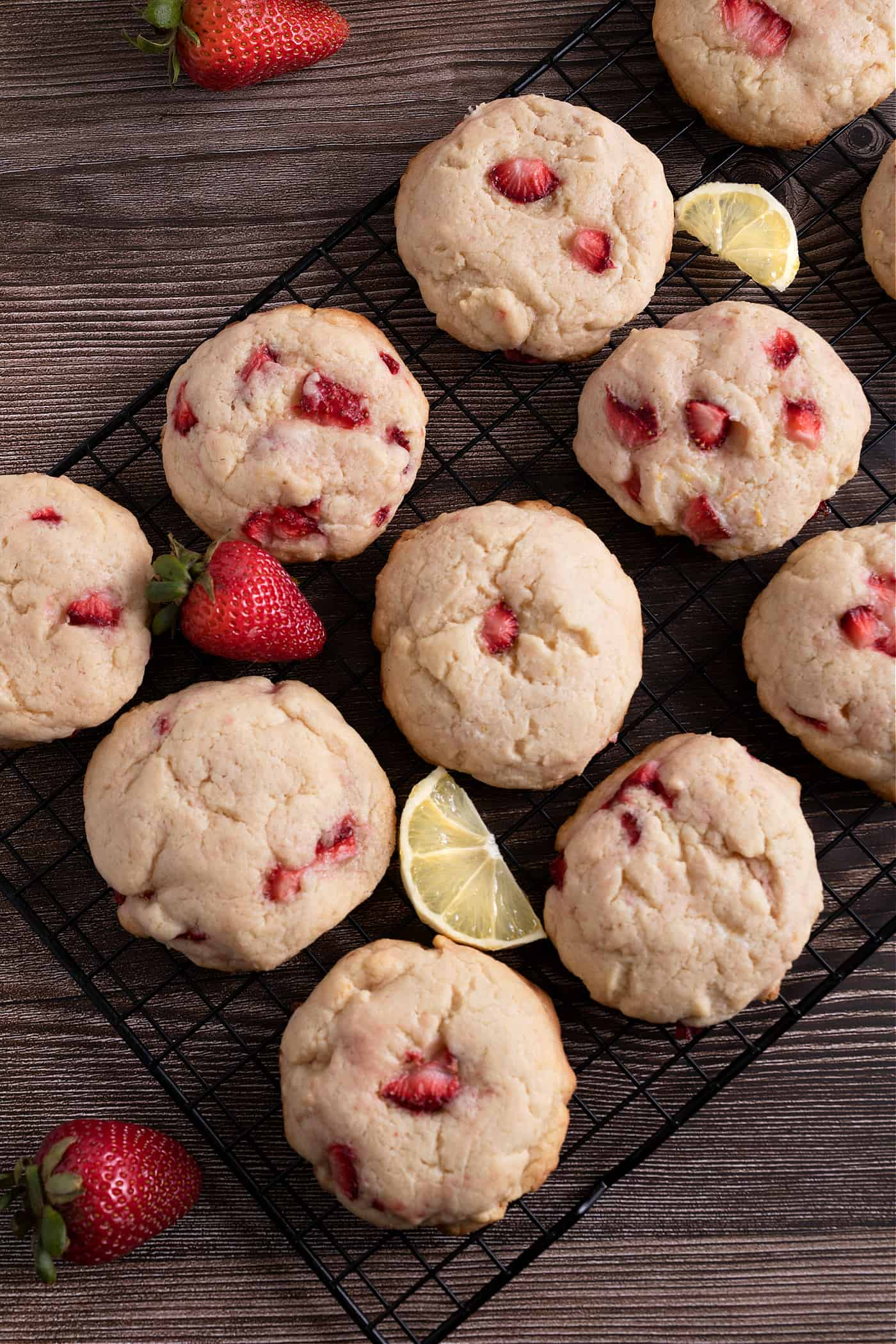strawberry lemonade cream cheese cookies on a cooling rack with fresh berries and lemon