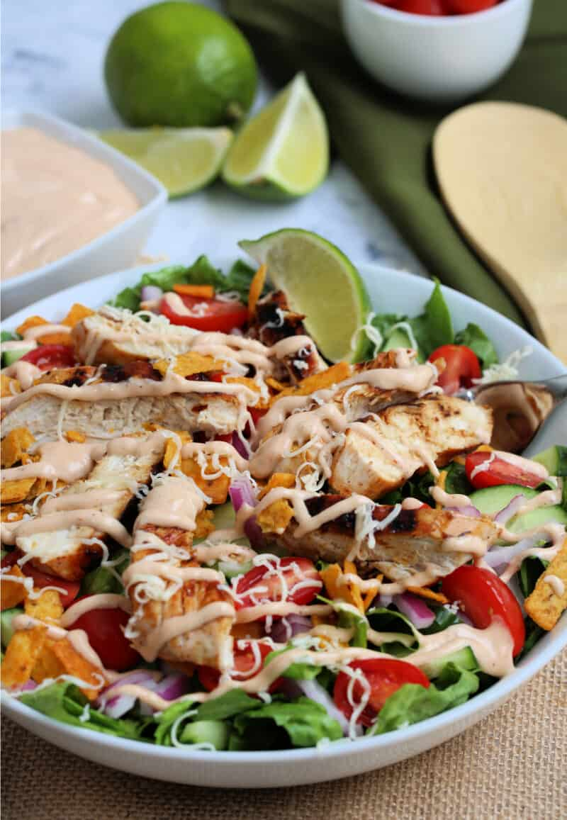 grilled chicken and vegetables in a salad in a bowl with dressing on it with a wooden spoon, dressing and lime wedges on the table