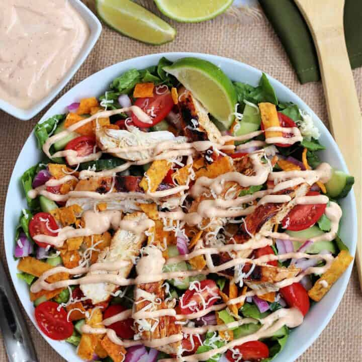 bbq chicken salad with a lime wedge in a bowl with a wooden spoon beside it