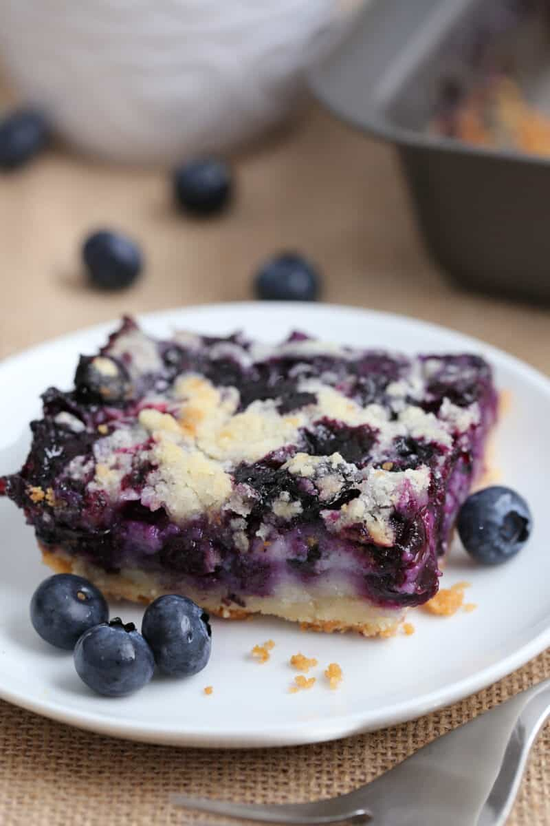 a blueberry pie bar dessert on a white plate surrounded with fresh blueberries