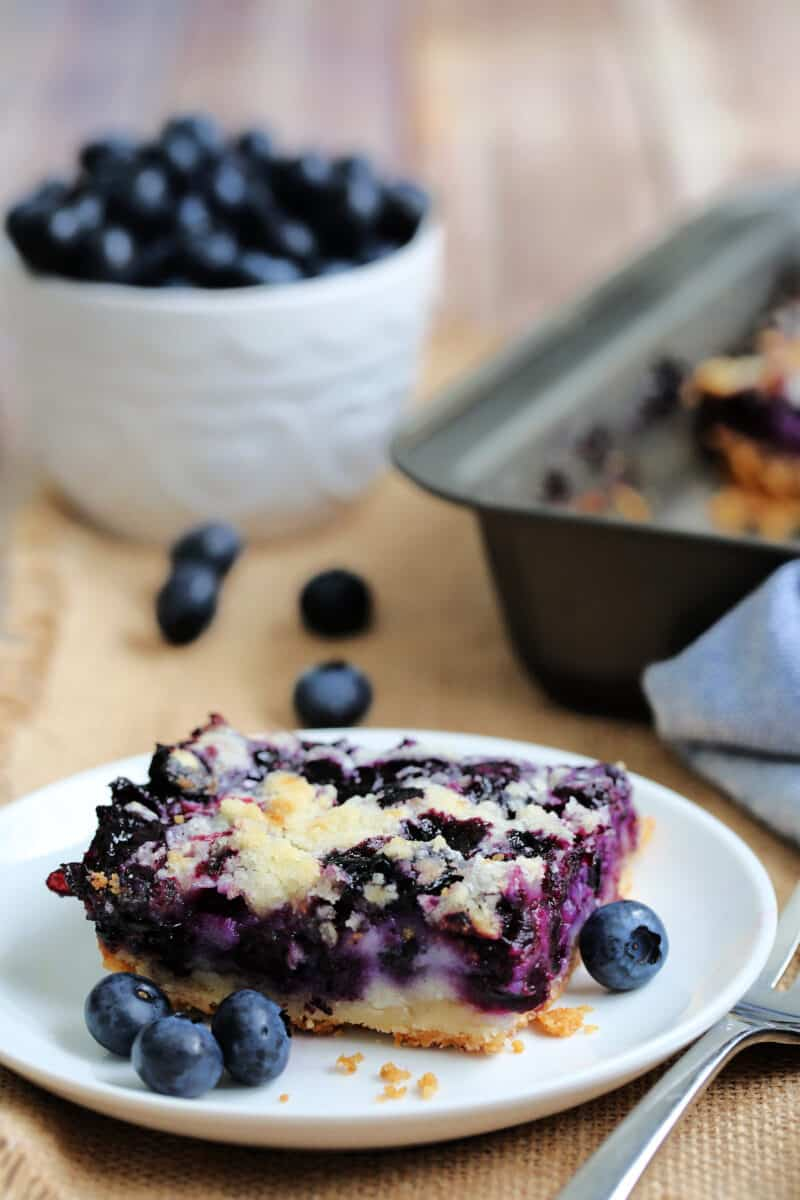 a slice of blueberry square on a white plate with berries surrounding it