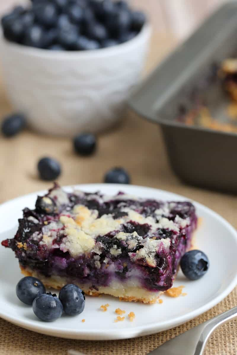 a slice of blueberry bar dessert on a plate with fresh blueberries