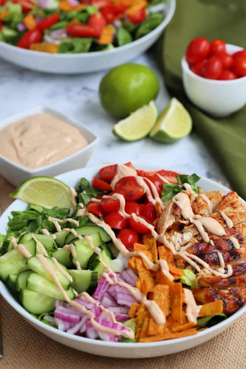 bbq chicken salad in a bowl with dressing drizzled on it with lime and dressing in the background