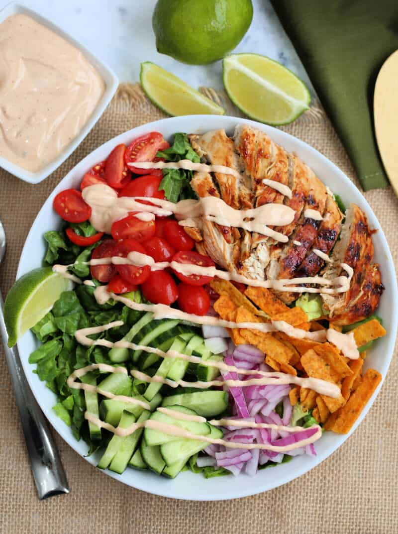 vegetables and bbq chicken slices in a bowl drizzled with dressing with lime wedges and a dish of dressing