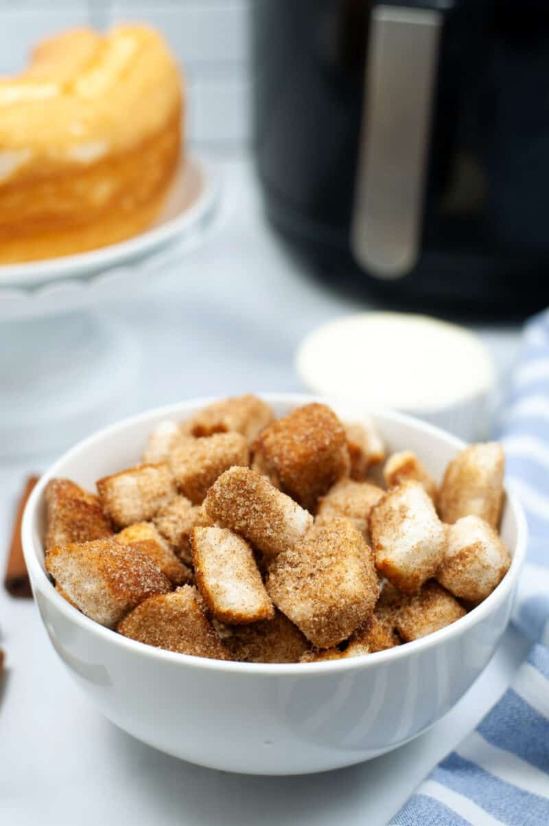 white bowl filled with churro dessert pieces on a table with an air fryer and cake behind it