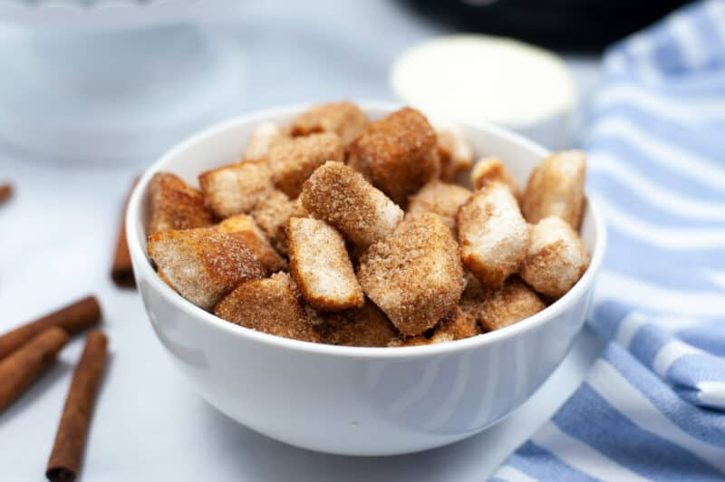 white bowl of churro dessert pieces with sticks of cinnamon beside them