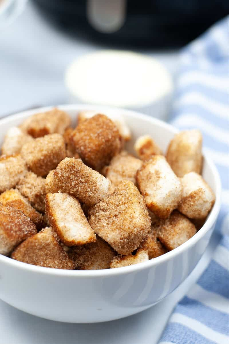 a white bowl of churro dessert pieces beside a blue and white cloth with an air fryer in the background