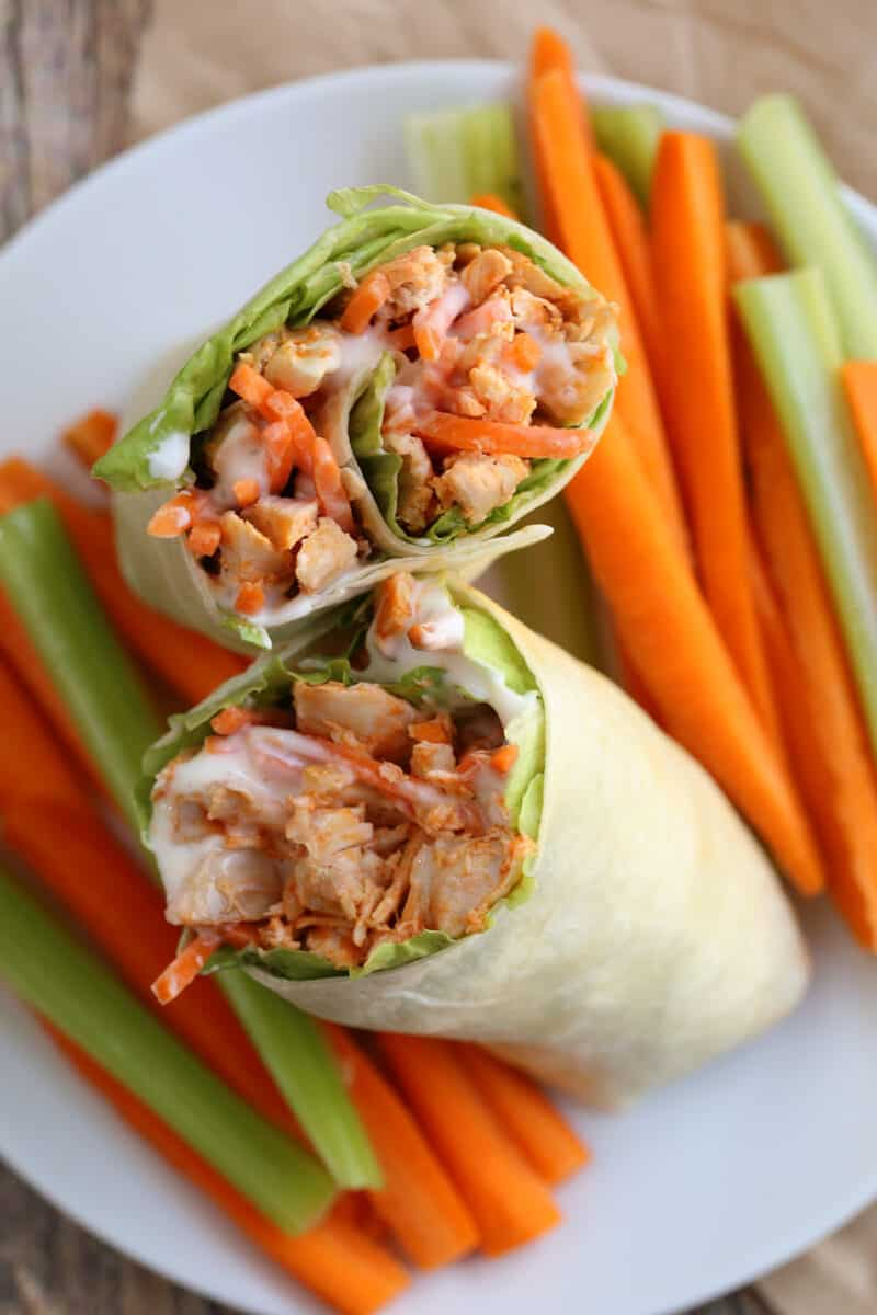 two chicken wraps on a plate surrounded by cut raw vegetables