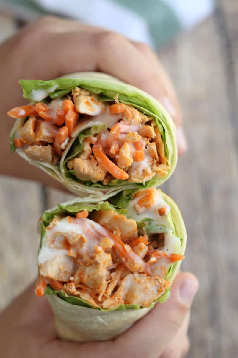 two buffalo chicken wraps being held with hands