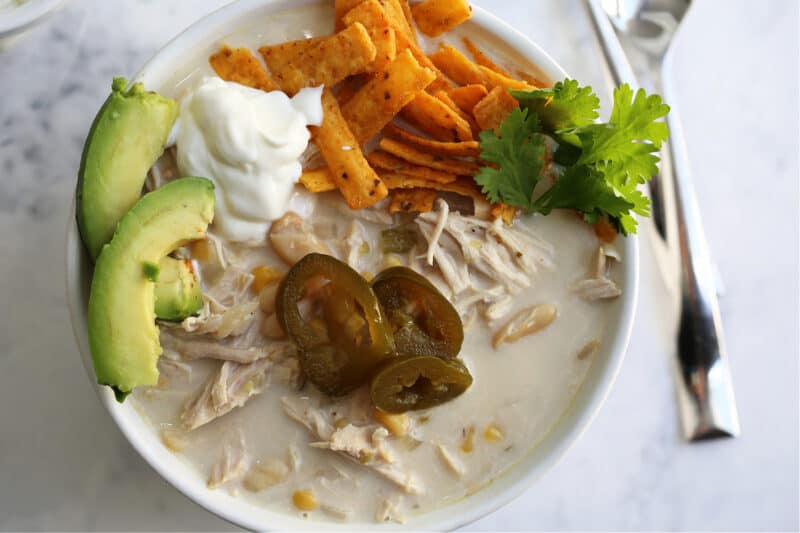 a top view of white chicken chili in a bowl with avocado, sour cream, jalapeños and cilantro