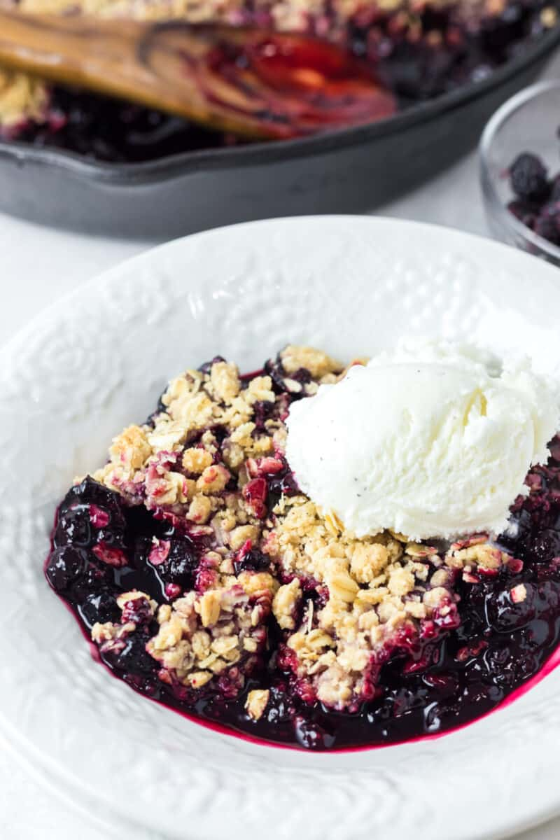 raspberry crisp in a white bowl with vanilla ice cream on top