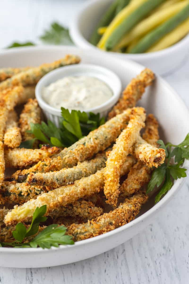 closeup photo of fried green beans in a white bowl with parsley