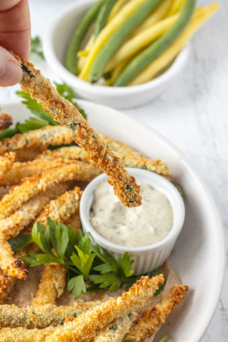 coated air fried green bean held over a white bowl of dip