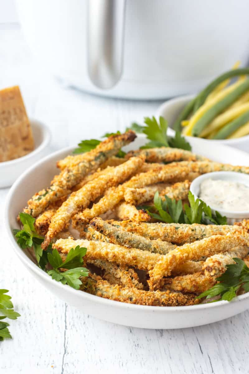 white bowl of fried green beans with parsley on a white table