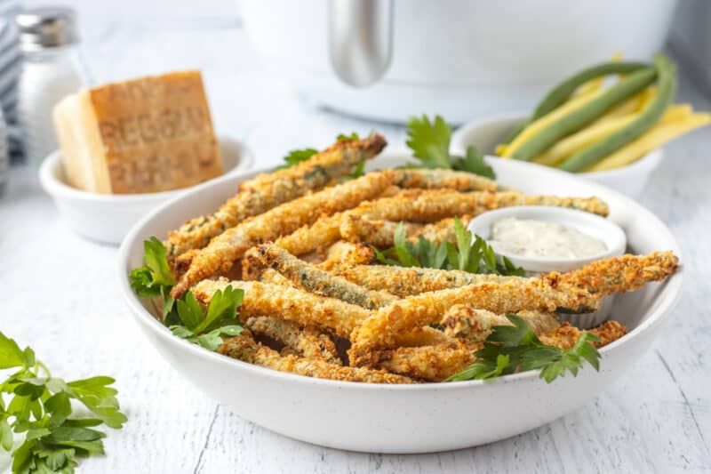 a white bowl full of fried green beans with parsley and ranch dressing in a white bowl
