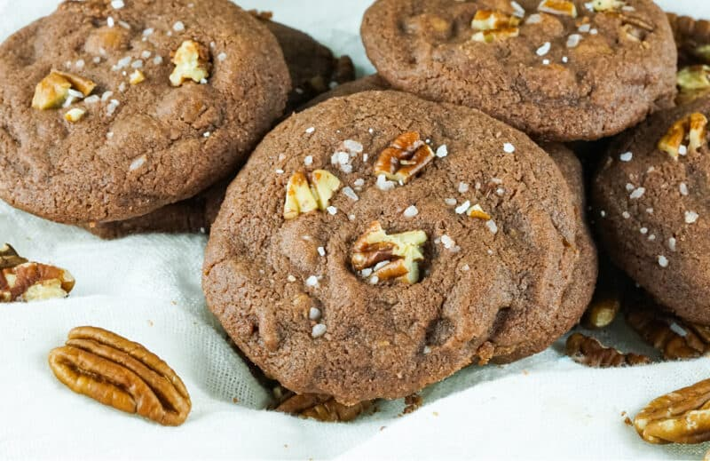 salted caramel chocolate cookies with pecans around them