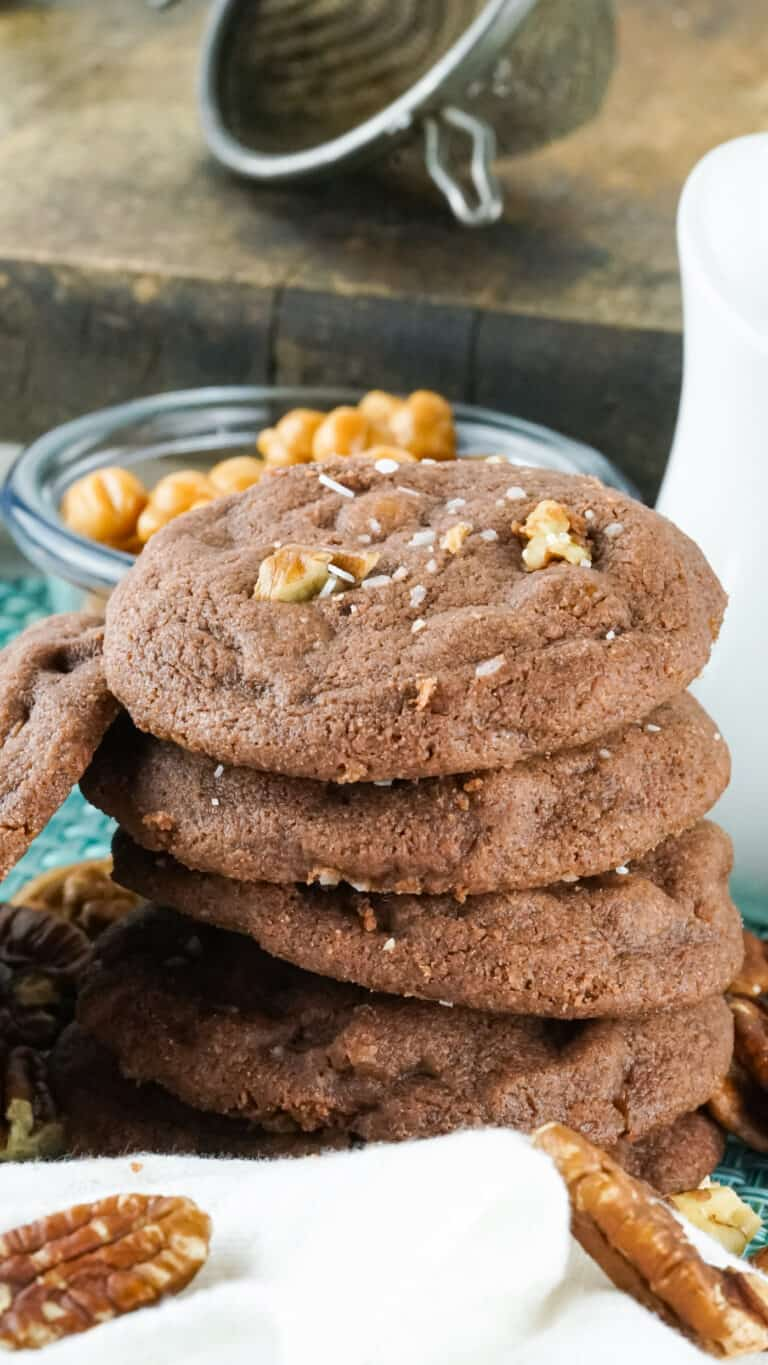 a stack of salted caramel chocolate chip cookies beside a bowl of caramels