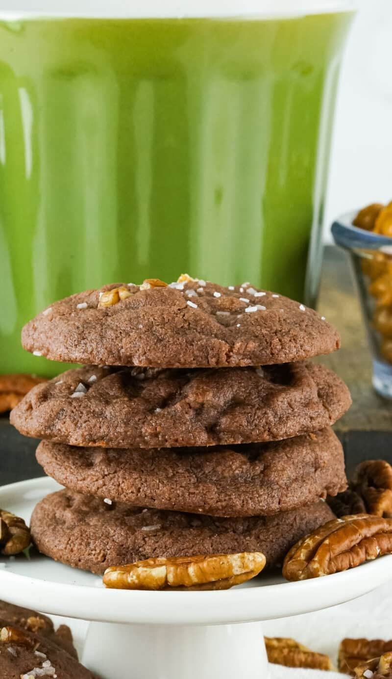 a stack of 4 chocolate chip cookies in from of a green mug with pecans around them