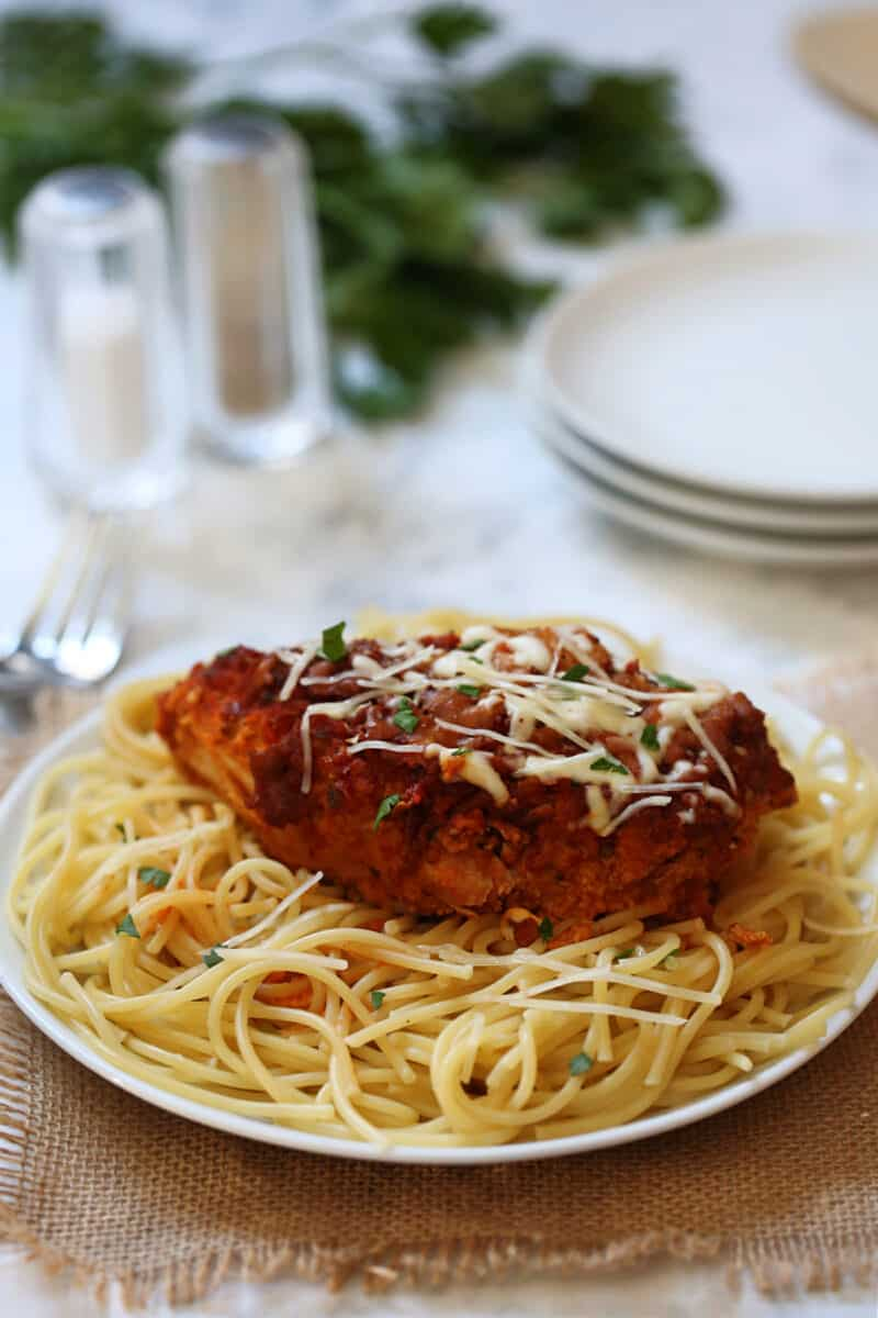 a whole piece of chicken parmesan on top of spaghetti on a white plate on a table