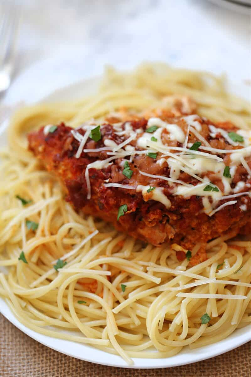 a whole piece of chicken parmesan on top of spaghetti on a white plate