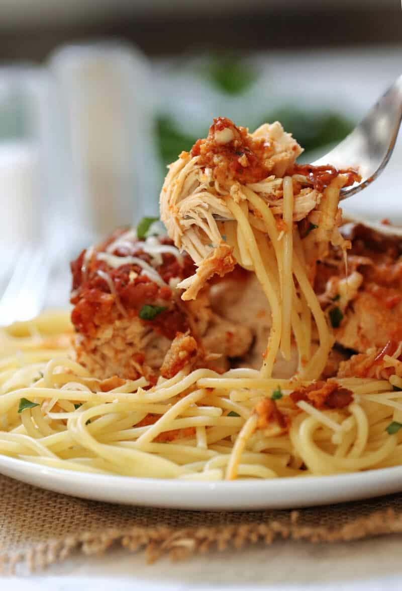 chicken parmesan and spaghetti being lifted by a fork on a plate